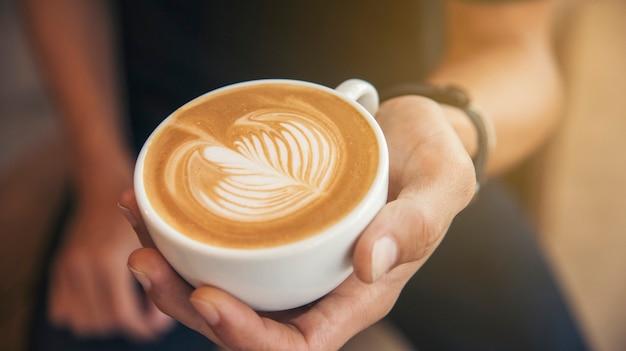 Late art een kopje koffie op barista handen