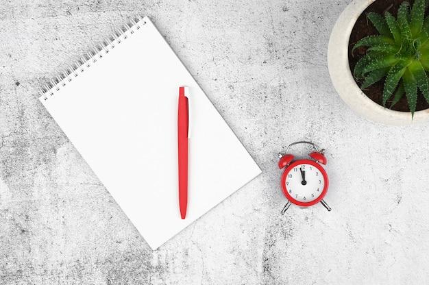 Late tijd op de klok. slimme telefoon, rode wekker en notebook op houten ruimte. termijn concept.