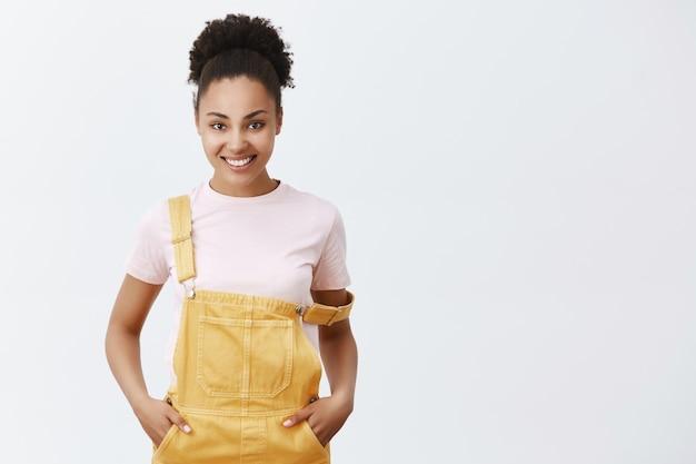 Laten we beginnen de wereld te veranderen. portret van charmante zelfverzekerde en vrolijke afro-amerikaanse vrouw in gele tuinbroek, met riem op schouder, hand in hand in de zakken en breed glimlachend, klaar voor actie