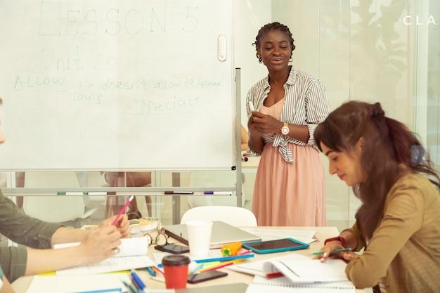 Laten we beginnen. vrolijke lerares met een donkere huid die glimlach op haar gezicht houdt terwijl ze met haar leerlingen communiceert