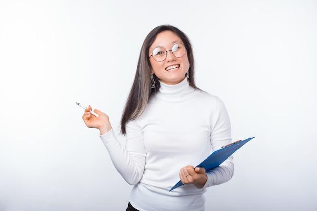 Laten we de checklist invullen. het portret van een vrolijke jonge vrouw houdt een karton en een pen.