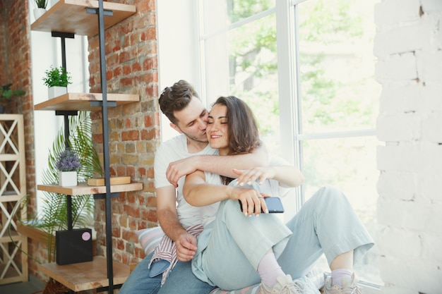 Laten we dit moment bekijken. jong stel verhuisde naar een nieuw huis of appartement. zie er gelukkig en zelfverzekerd uit. familie, verhuizen, relaties, eerste huisconcept. bij het raam zitten, knuffelen en selfie maken.