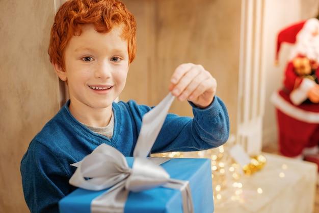 Laten we eens kijken wat er in zit. leuke vrolijke jongen met een vrolijke glimlach op zijn gezicht zittend naast een open haard en het openen van een kerstcadeau.