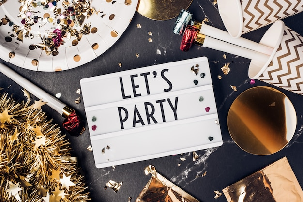 Laten we feesten op een lichtbak met feestbeker, feestblazer, klatergoud, confetti