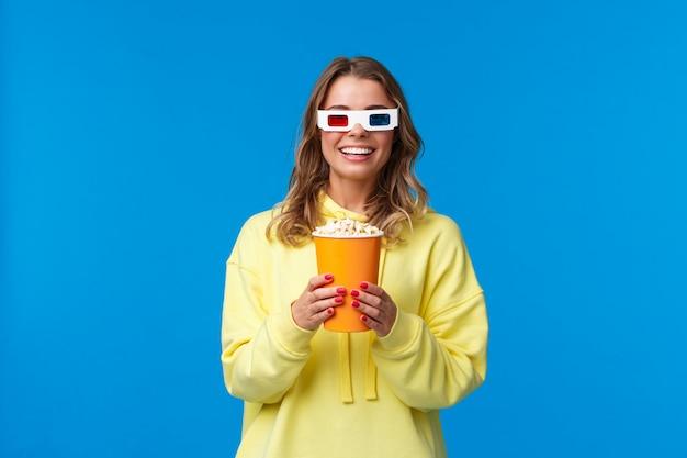 Laten we film kijken. opgewonden schattig jong blond meisje in 3d-bril, met popcorn en glimlachend geamuseerd als genietend van de première van film in de bioscoop, vermaakt over blauwe muur