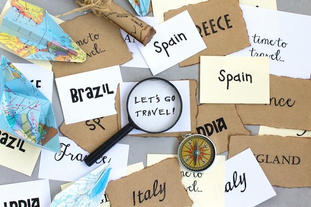 Laten we gaan reizen tekst woorden, land selectie, kaart vergrootglas kompas, grijze achtergrond