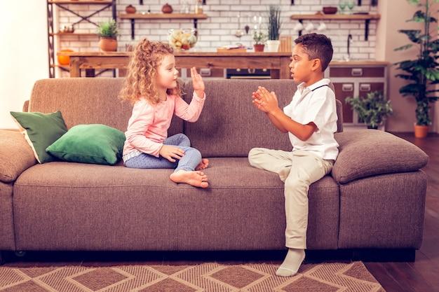 Laten we gaan spelen. charmant meisje met krullend haar dat in halve positie zit en met haar vriend praat