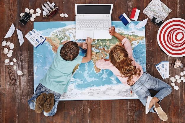 Laten we kinderen die op de wereldkaart liggen in de buurt van reisartikelen controleren en op een speelgoedcomputer spelen