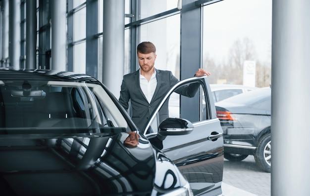 Laten we naar de baan gaan. moderne stijlvolle bebaarde zakenman in de auto-sedan
