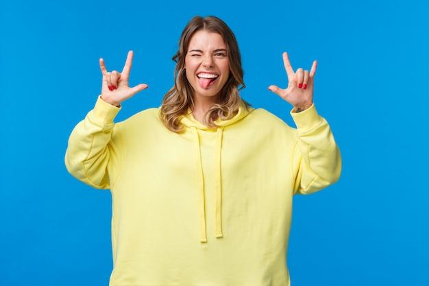 Laten we plezier hebben. zorgeloos vrolijke knappe blonde vrouw in gele hoodie met rock-n-roll-teken en tong als opgewonden en blij met geweldig feest, dans geniet van concert