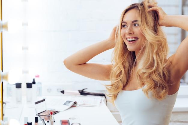 Laten we spelen met mijn look! zijaanzicht van een mooie jonge vrouw die naar haar spiegelbeeld kijkt en haar handen in het haar houdt terwijl ze aan de kaptafel zit
