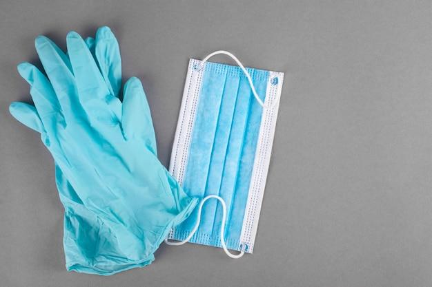 Latex medische handschoenen en masker op een grijze achtergrond.