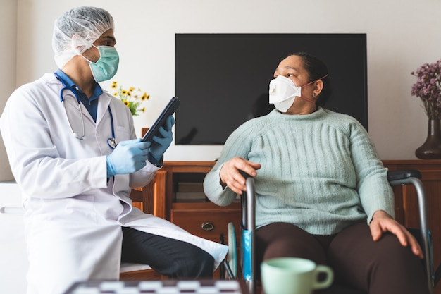 Latijns-amerikaanse arts die patiënt thuis besmet met covid-19 controleert.