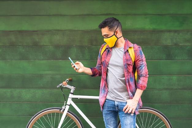 Latijns-amerikaanse jongeman masker dragen en telefoon buitenshuis gebruiken.