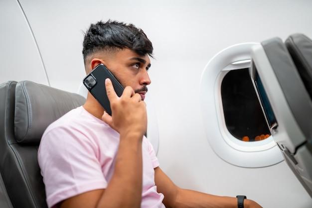 Latijns-amerikaanse jongeman praat op de mobiele telefoon terwijl hij in het vliegtuig bij het raam zit