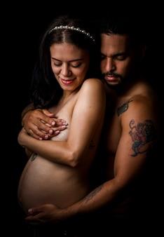 Latijns-amerikaanse koppels met de vrouw zwanger en knuffelen elkaar op zwarte achtergrond