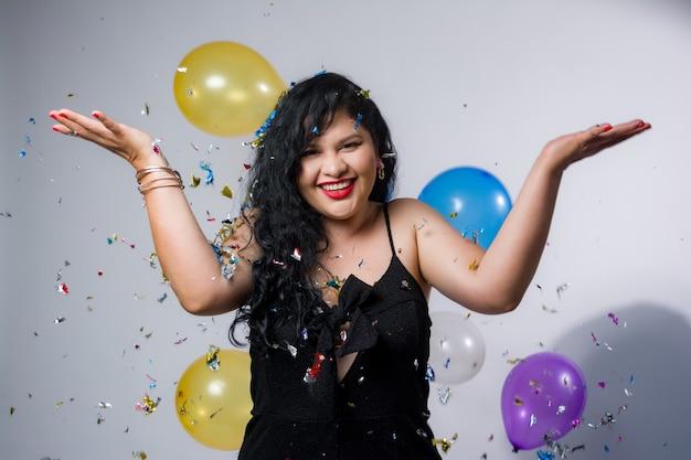 Latijns-amerikaanse meisjes poseren en vieren het nieuwe jaar met ballonnen en confetti