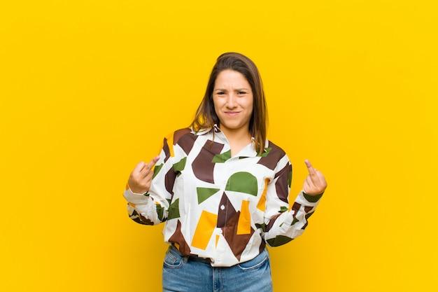 Latijns-amerikaanse vrouw die zich provocerend, agressief en obsceen voelt, de middelvinger omdraait, met een rebelse houding over de gele muur
