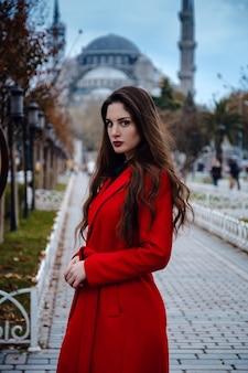 Latijns-amerikaanse vrouw of turkse vrouw in een rode stijlvolle jas voor de beroemde blauwe moskee in istanbul