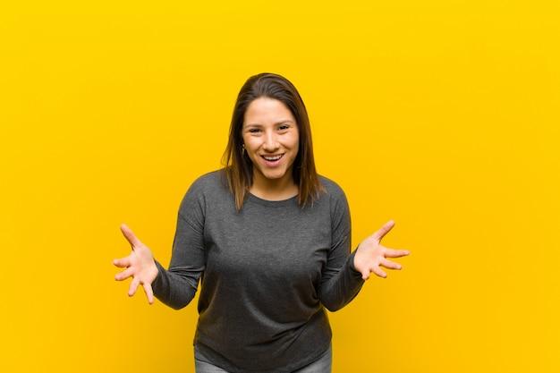 Latijns-amerikaanse vrouw voelt zich gelukkig, verbaasd, gelukkig en verrast, zoals serieus omg zeggen? ongelofelijk geïsoleerd op gele muur