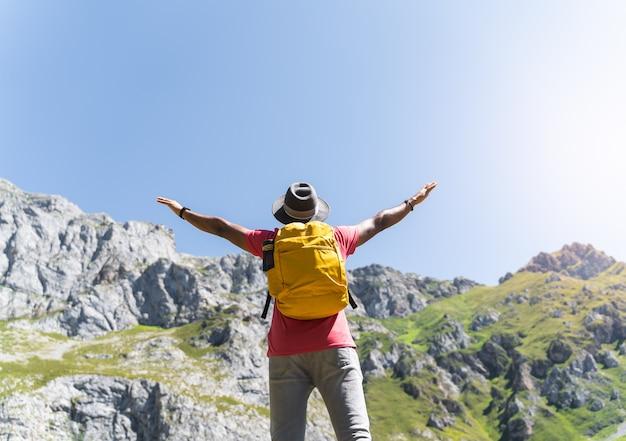 Latijns-man handen omhoog kijken naar de berg.