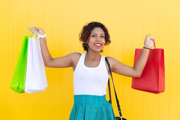 Latijns meisje glimlacht en pronkt met haar aankoop op gele achtergrond.