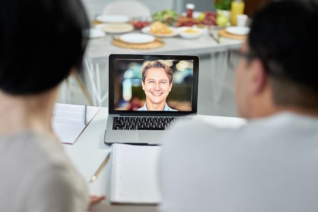 Latijns paar dat videogesprek voert met huwelijksconsulent met behulp van laptop, kijkend naar scherm, pratend op webcam. online overlegconcept. focus op laptopscherm