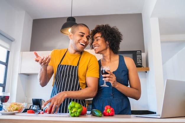 Latijns paar die laptop met behulp van terwijl het koken in keuken.