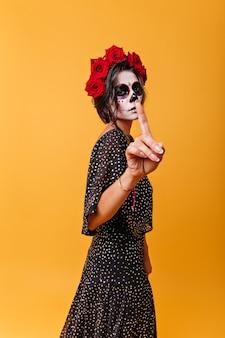 Latijns schoonheidsmeisje met make-up in vorm van traditioneel beeld van schedel vraagt om stil te zijn, wijsvinger tonen