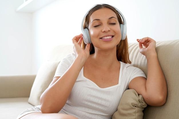 Latijns-tiener ontspannen en luisteren naar muziek met een draadloze koptelefoon thuis