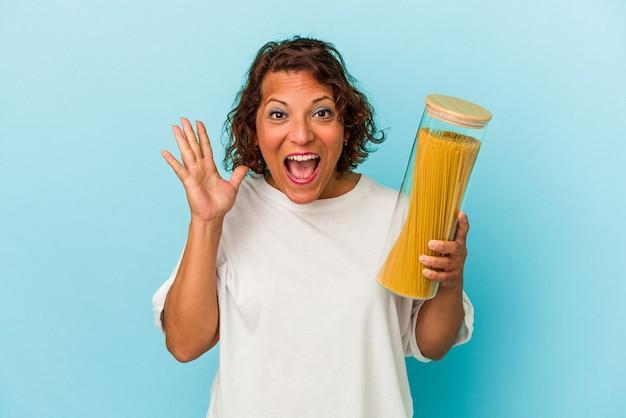 Latijns-vrouw van middelbare leeftijd met pasta pot geïsoleerd op blauwe achtergrond verrast en geschokt.