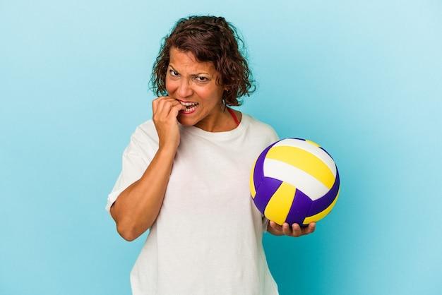 Latijns-vrouw van middelbare leeftijd volleyballen geïsoleerd op blauwe achtergrond vingernagels bijten, nerveus en erg angstig.