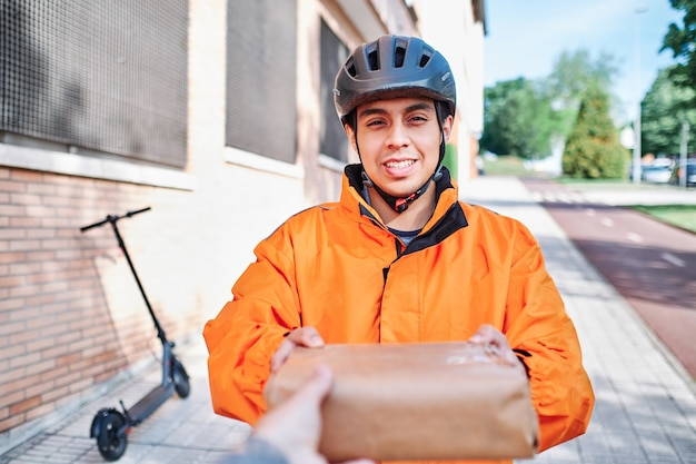 Latijnse bezorger op elektrische scooter bezorgt de ontvanger met de hand