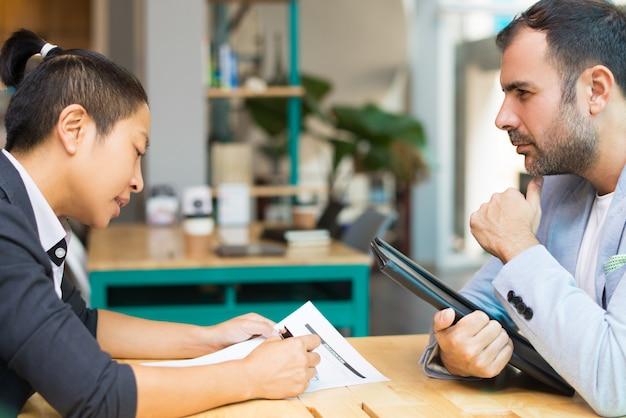 Latijnse en aziatische managers zitten en werken met documenten op kantoor