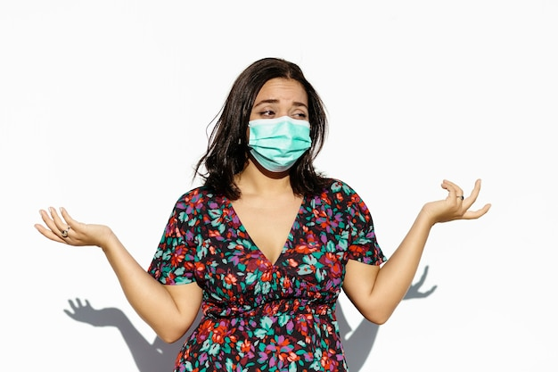 Latijnse en natuurlijke jonge vrouw die een gezichtsmasker draagt op een witte achtergrond. ze heeft een gebaar van verontwaardiging.