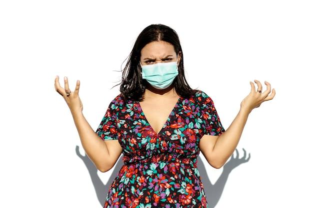 Latijnse en natuurlijke jonge vrouw die een gezichtsmasker draagt op een witte achtergrond. ze heeft een pissig gebaar