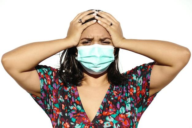 Latijnse en natuurlijke jonge vrouw die een gezichtsmasker draagt op een witte achtergrond. ze ziet er moe en ziek uit.