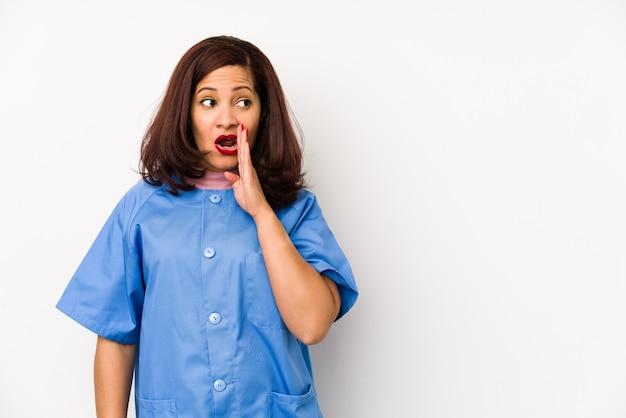 Latijnse geïsoleerde verpleegstersvrouw van middelbare leeftijd die een geheim heet het remmen nieuws zegt en opzij kijkt