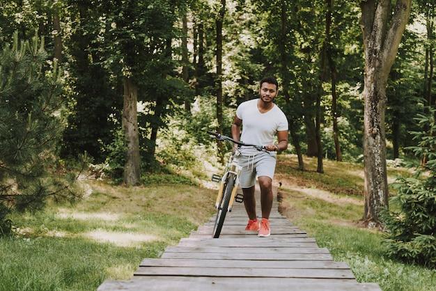Latijnse kerel in park die met fiets loopt
