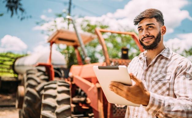 Latijnse landelijke zakenman die het werk in digitale tablet controleert.