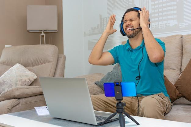 Latijnse man die een online cursus volgt vanaf de bank van zijn huis (concept van online cursus en hoger onderwijs)