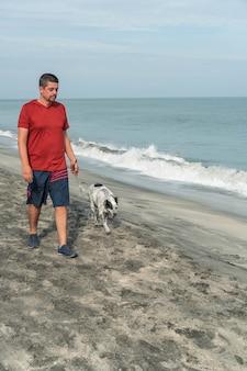 Latijnse man die 's ochtends met een hond op het strand loopt