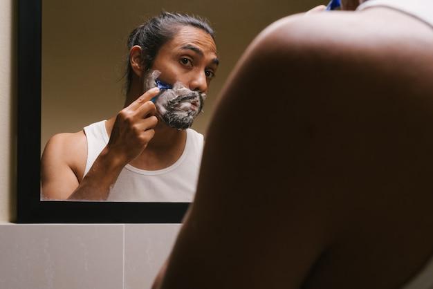 Latijnse man die zich in zijn badkamer scheert