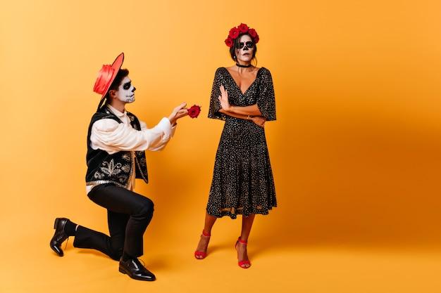 Latijnse man verliefd staande op knie naast zijn vriendin. vrolijke zombiekerel met roos poseren op gele muur met donkerbruin meisje.