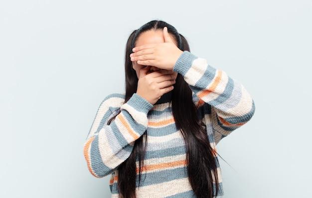 Latijnse vrouw bedekt gezicht met beide handen en zegt nee tegen de voorkant! afbeeldingen weigeren of foto's verbieden