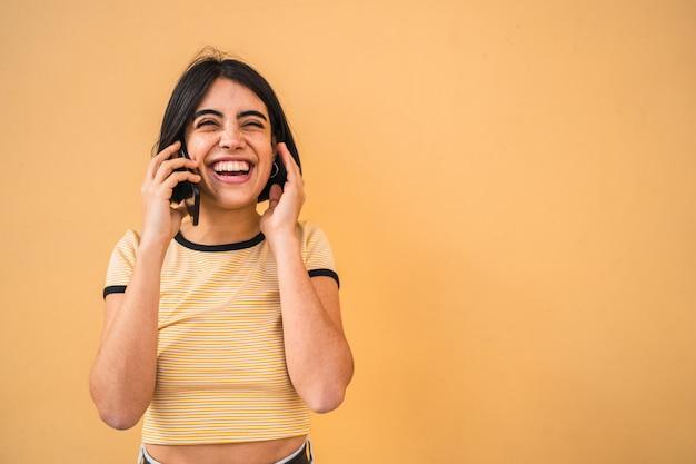 Latijnse vrouw die aan de telefoon spreekt.