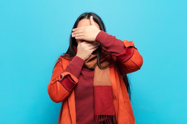 Latijnse vrouw die gezicht bedekt met beide handen en nee zegt tegen de camera! foto's weigeren of foto's verbieden