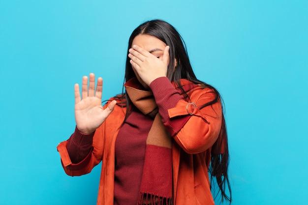 Latijnse vrouw die gezicht bedekt met hand en andere hand naar voren zet om de camera te stoppen, foto's of afbeeldingen weigeren