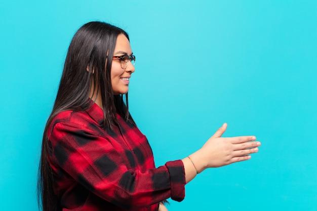 Latijnse vrouw die lacht, je begroet en een hand schudt om een succesvolle deal, samenwerkingsconcept te sluiten