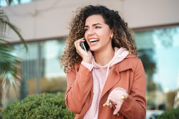 Latijnse vrouw die lacht terwijl ze buiten op straat telefoneert. stedelijk begrip.